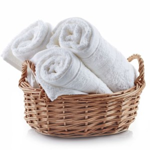 white spa towels in a basket isolated on white background