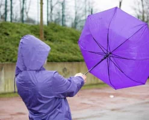 Young-person-fighting-in-wind-with-umbrella