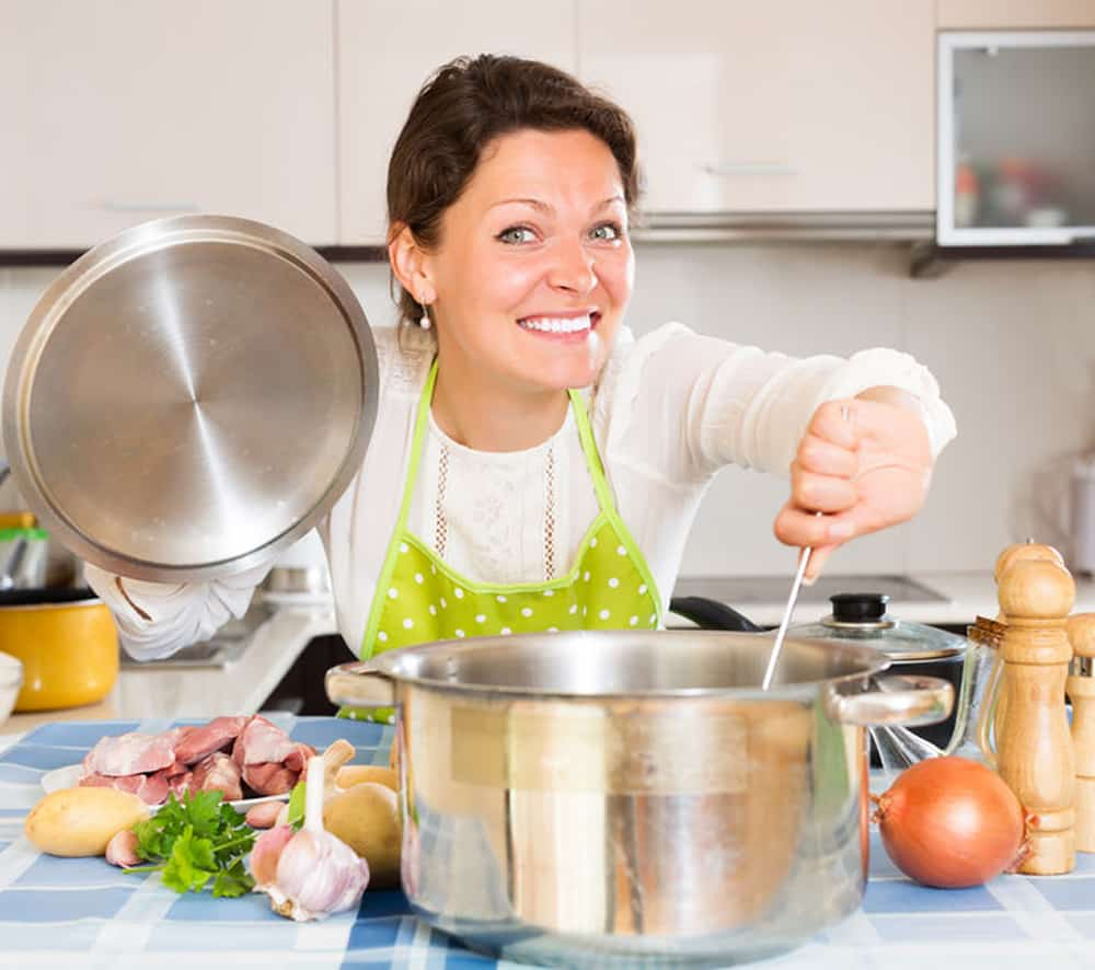 Young woman wearing an apron cooking a big pot of soup