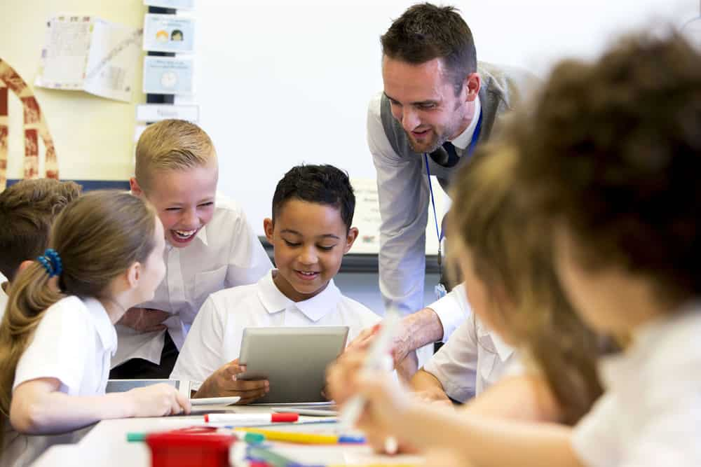 A male teacher sits supervising a group of children who are working on whiteboards and digital tablets