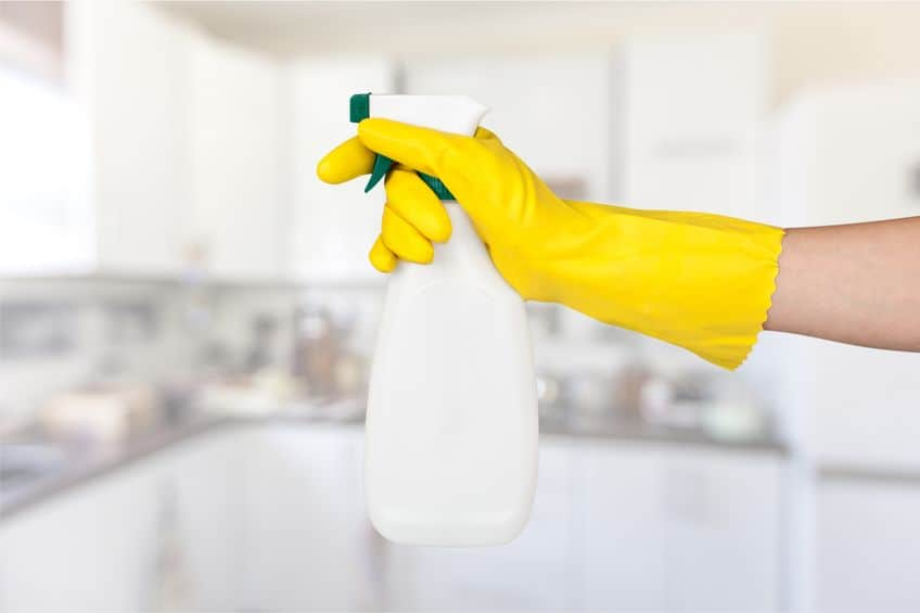 female hand in yellow rubber glove holding spray bottle of homemade cleaning solution