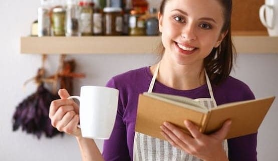 A woman holding a cup, with Gift and Cookbook