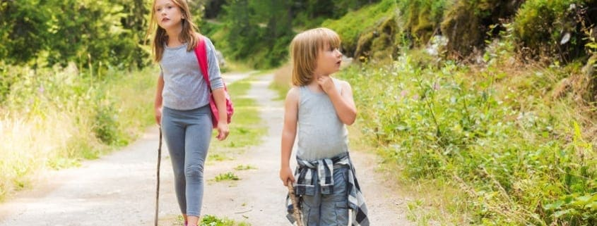Two cute kids hiking in the forest depicting the need to be able to survive a crisis