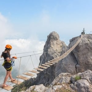 young-woman-crossing-the-chasm-on-rope-bridge