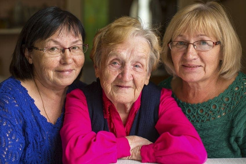 elderly woman with two adult daughters