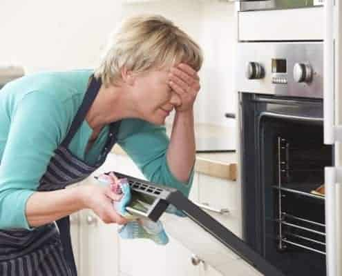 Woman Looking In Oven And Covering Eyes Over Disasterous Meal