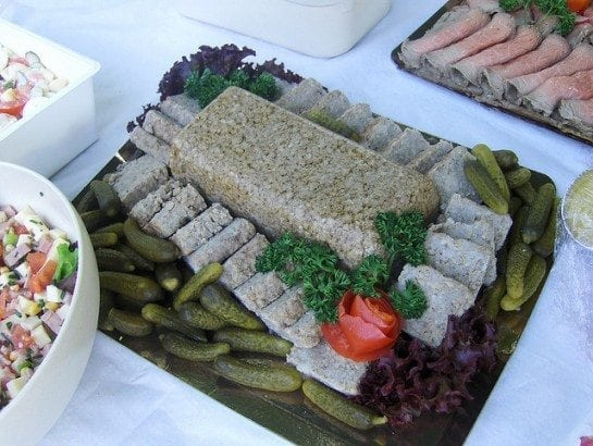 A plate of food with a slice of cake on a table, with Pâté