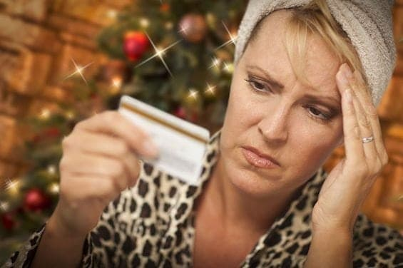 48617473 - very upset woman holding credit card in front of christmas tree.