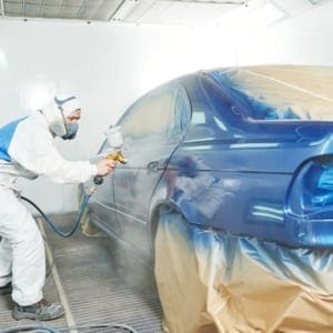 Trade school student painting car