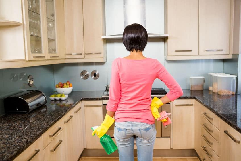 Rear view of standing brunette ready to clean the kitchen with yellow gloves