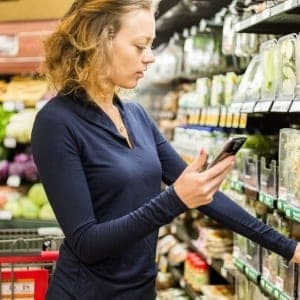 Young woman shopping in the fresh produce section at the grocery store.