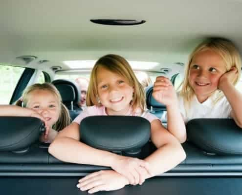 Three smiling children back seat of car on family vacation