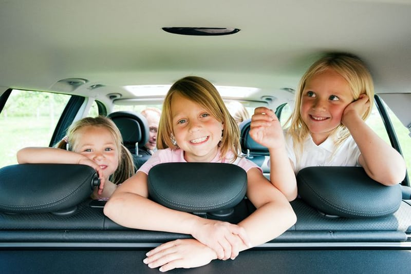 Three happy children back seat of car on family vacation