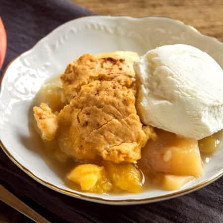 Bowl of homemade peach cobbler with vanilla ice cream