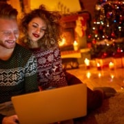 Young couple looking on laptop on Christmas eve to see that everything is paid in full