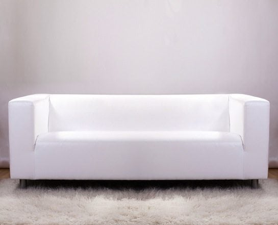 White couch on white rug in white room