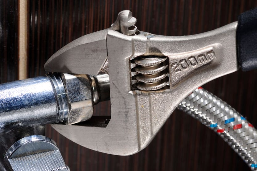 Closeup of wrench tightening washing machine hose connector