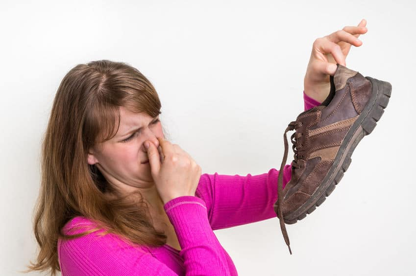 Woman holding up stinky shoe