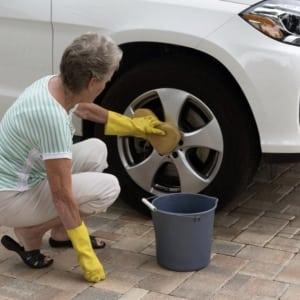 older-woman-washing-car-on-driveway