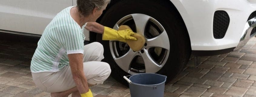 older-woman-washing-car-on-driveway