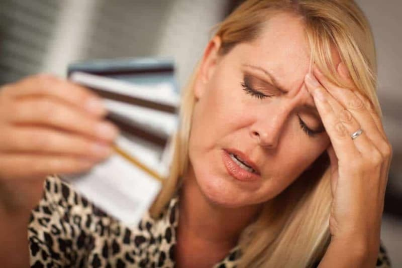 Woman with credit card woes, hand on forehead to ease the headache