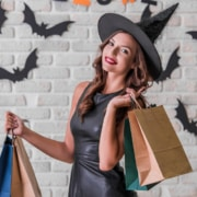 girl in black dress and witch hat holding shopping bags, looking at camera and smiling