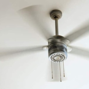 Ceiling fan is rotating at the ceiling of the room.