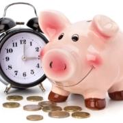 A close up of a piggy bank and a clock
