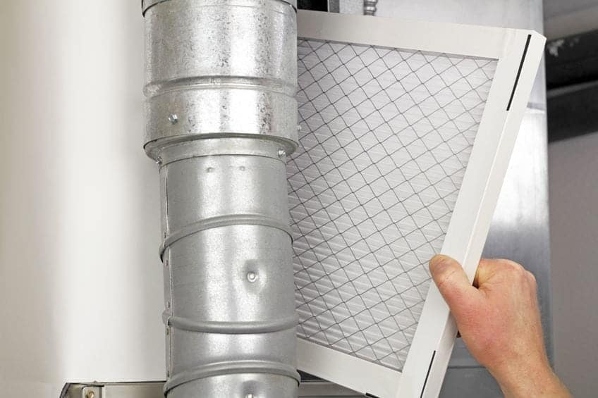 male-arm-and-hand-replacing-disposable-air-filter-in-residential-air-furnace.