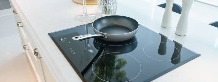 Modern black smooth glass cooktop on white quartz counter