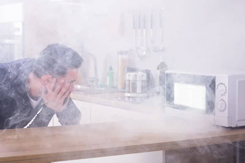 Unhappy young man looking at fire coming from microwave oven in kitchen