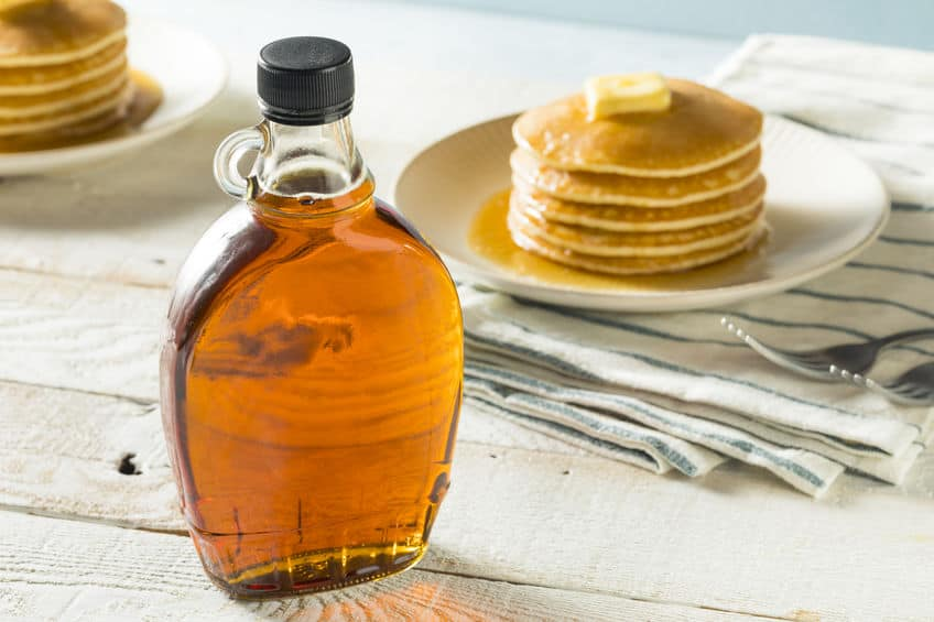 A cup of coffee on a table, with Honey and Syrup