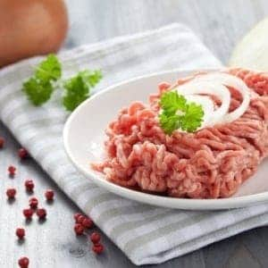plate of raw ground beef with raw onion garnish