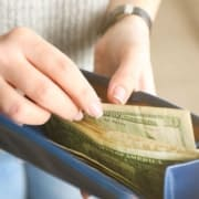 Girl with blue wallet showing her pulling out $10 bill