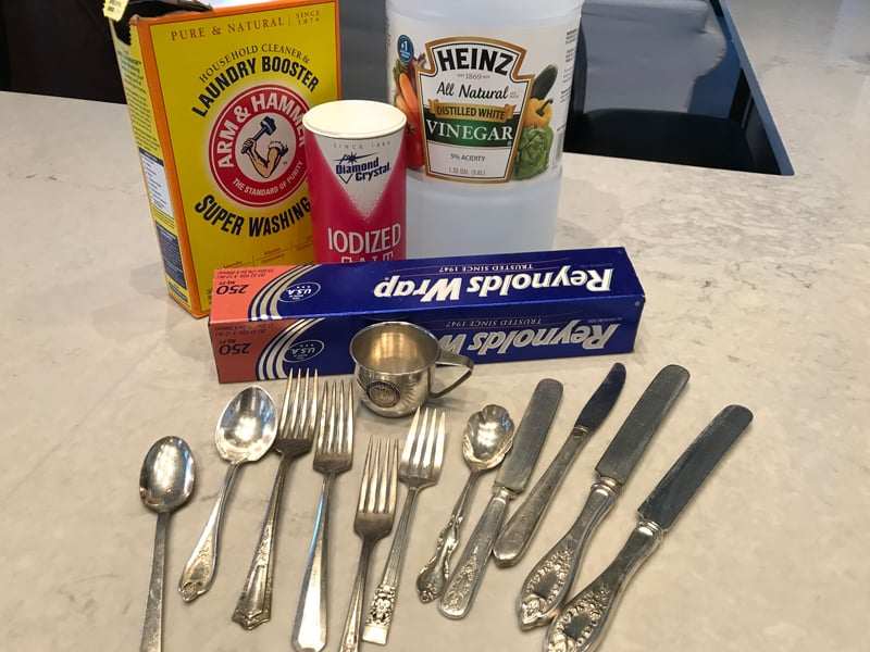 The ingredients required for homemade silver cleaner and tarnish remover together with the cleaned flatware