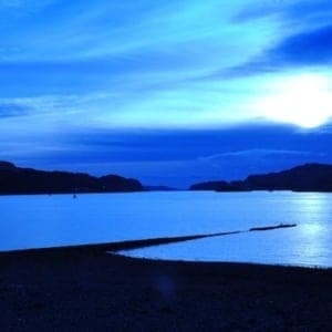 Beautiful, blue dawn over a lake and mountains.
