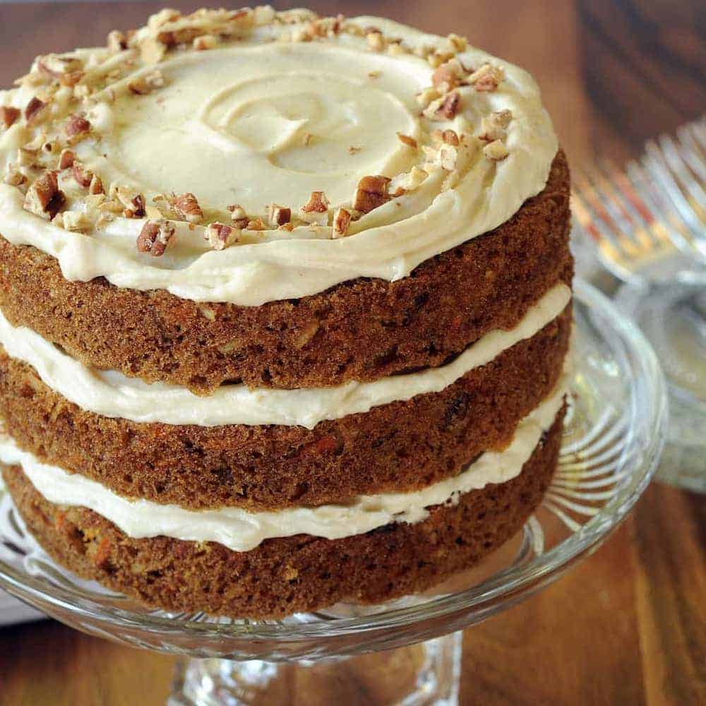 scrumptious-3-layer-carrot-cake-sitting-on-glass-cake-stand-creamy-frosting-and-sprinkling-of-walnuts
