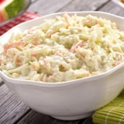 A bowl of rice on a plate, with Coleslaw