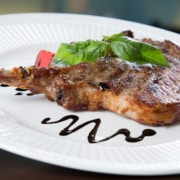 Pork chop on a white plate covered with Apricot Hoisin sauce