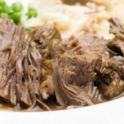 sliced pot roast dinner on a plate with mashed potatoes