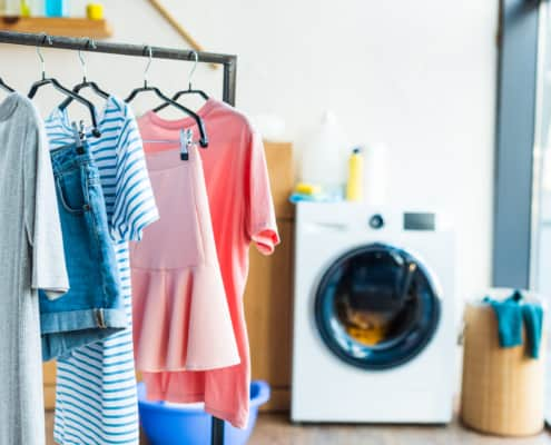 laundry day with clean clothes on hanging rack and dryer in the background