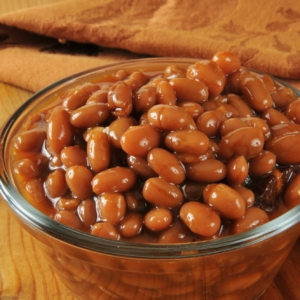A cup of baked beans on a rustic wooden table