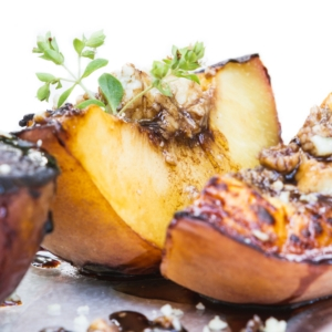 close up of grilled peaches with blue cheese and a balsamic reduction on a white background