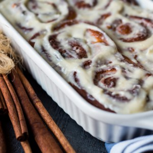 Cinnabon buns with cinnamon in baking dish on a wooden board