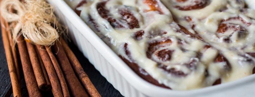Cinnabon buns with cinnamon in baking dish on a wooden board