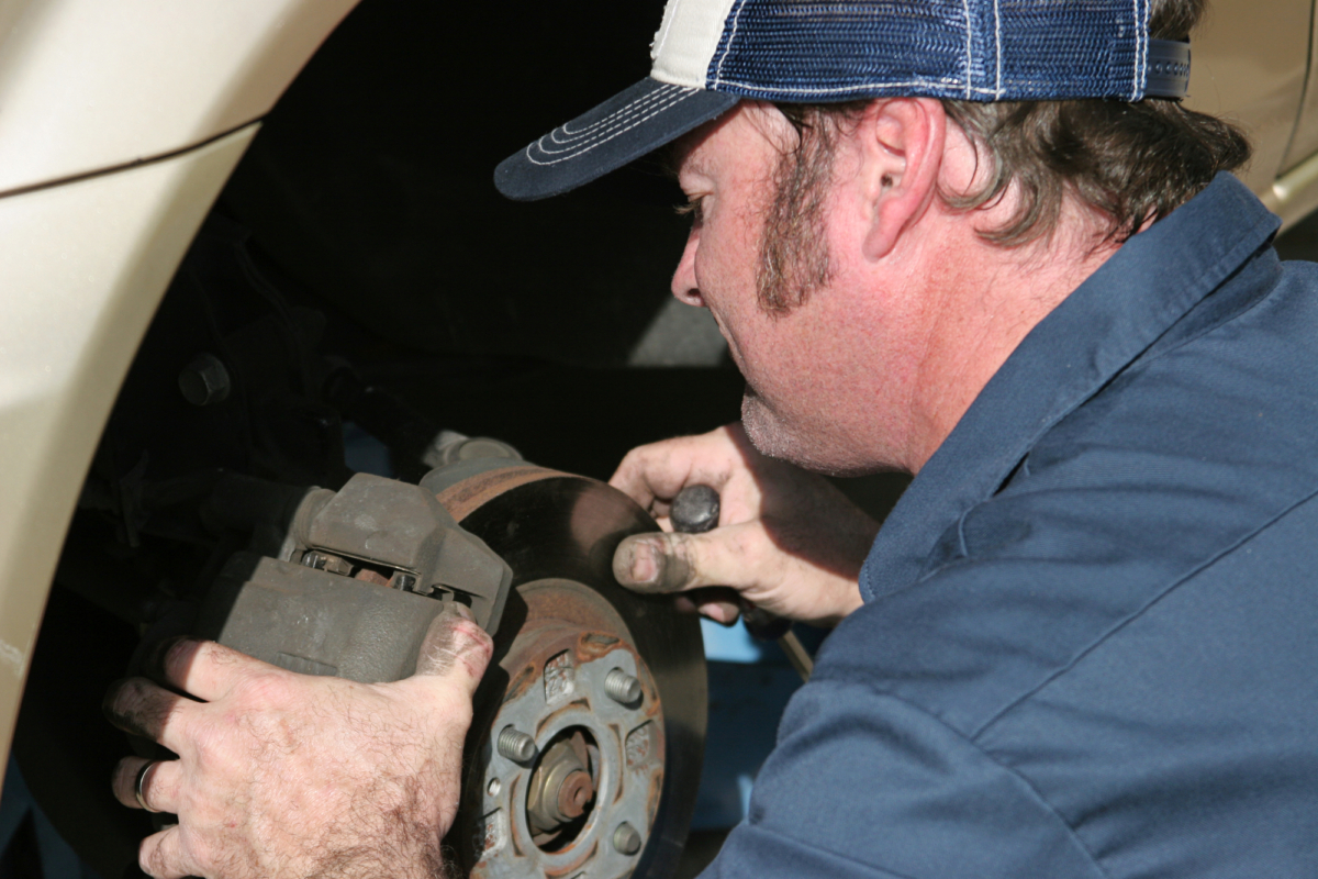auto mechanic at work cleaning and repairing brakes