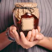 peach raspberry homemade jam in hands of woman