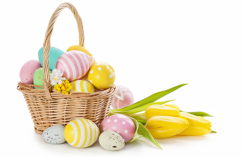 Basket with boiled and decorated easter eggs on white background