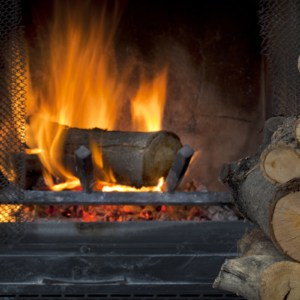 Fire in fireplace with a pile of log firewood
