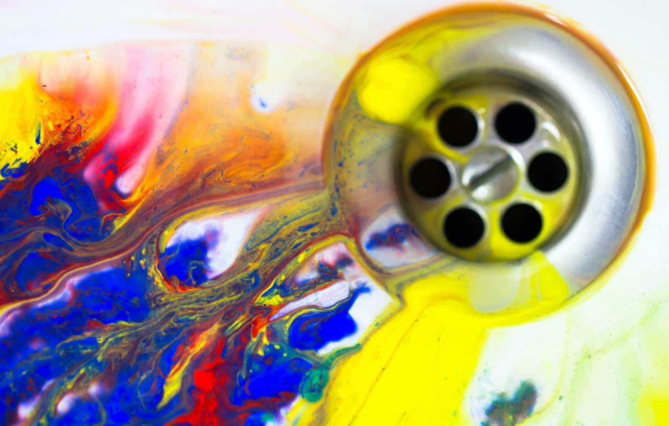 Liquid multicolor paint flow in sink drain as a creativity and art concept